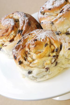 sultanas: Luscious apple scroll pastries, on a cake stand.