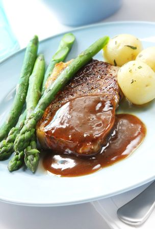 Beef steak with peppercorn sauce,  potatoes and asparagus. photo