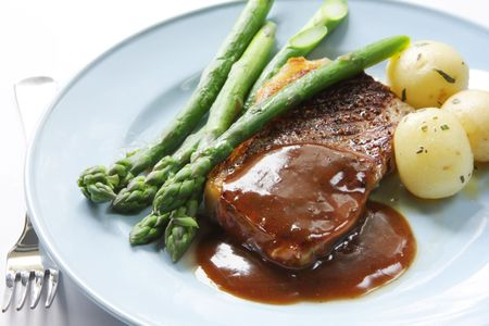 gravy: Beef steak with peppercorn sauce,  potatoes and asparagus.
