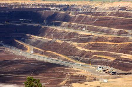 Open-cut brown coal mine, in dappled sunlight.