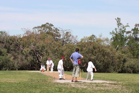 umpiring: Junior cricket, Australian style.  Under-12 team playing Saturday morning cricket, on a matting pitch.  One of the dads is umpiring, on a beautiful spring morning.