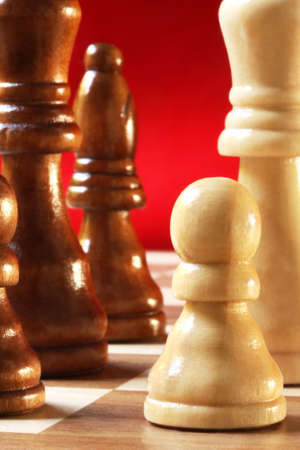 Wooden chess pieces in close-up, with red background photo