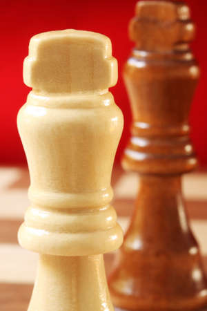 White wooden chess king in close-up, with red background photo
