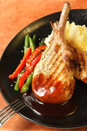 capsicum: Grilled pork cutlets with smokey barbecue sauce, potato mash, green beans and capsicum.