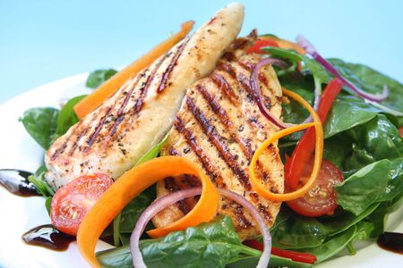 Grilled chicken breast with a spinach salad, with a balsamic reduction. Stock Photo