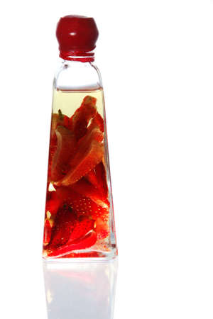 Olive oil infused with strawberries, in a fancy wax-sealed glass bottle.  Isolated on white, with reflection. Stock Photo - 2130714