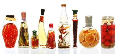 Variety of oil infusions and preserved fruits and vegetables, in fancy glass bottles.  Isolated on white, reflected.  XXL file.