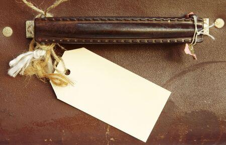 sconosciuto: Bianche etichetta bagaglio legato alla maniglia della valigia di cuoio vintage. Destinazione sconosciuta!