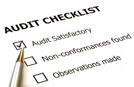 satisfactory: Audit checklist with silver and gold ballpoint.  Check in