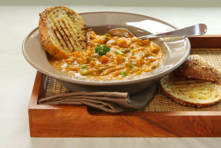 serving tray: Hearty minestrone pasta and vegetable soup, served with toasted wholegrain sourdough bread on a serving tray.