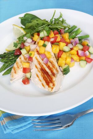 Grilled chicken with mango salsa, asparagus, and  spinach. photo