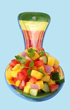 Mango salsa, on a brightly colored spoon, with blue background.  Serve with meat or fish, with tortilla chips or as a colorful bruschetta. photo