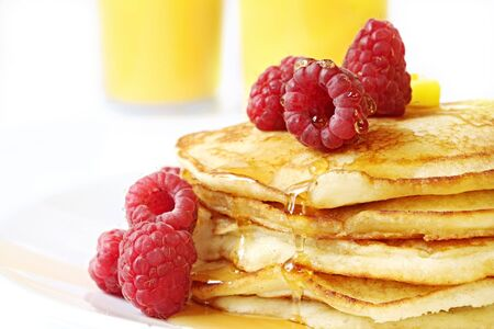 flapjacks: Pancake stack with fresh raspberries, maple syrup and butter.  Orange juice behind.  A delicious indulgent breakfast. Stock Photo
