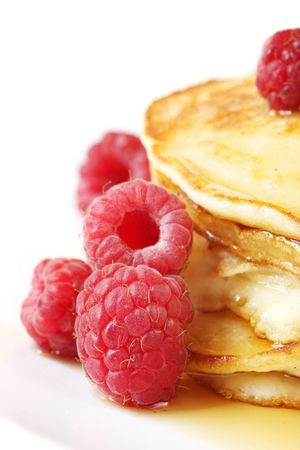 Pancakes with raspberries and maple syrup, in close-up.  High-key effect. photo