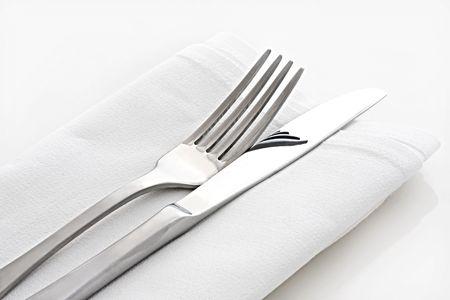 white linen: Plata cuchillo y tenedor sobre servilleta de lino blanco. Foto de archivo