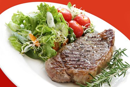 Grilled steak with salad.  Porterhouse or New York strip steak, grilled, with rosemary.  Served with salad of mixed greens, cherry tomatoes, sprouts, cucumber, celery, and carrot.  Vibrant red background.