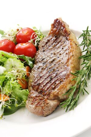 cherry tomatoes: Grilled steak and salad, on white plate.  Mixed lettuce and spinach leaves and cherry tomatoes, with sprouts and other good healthy vegetables.