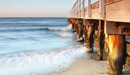 amanecer: Antiguo muelle en la luz dorada del amanecer. Long velocidad de obturaci�n desdibuja las olas rompiendo alrededor de pilones degradado.
