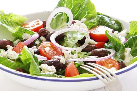 Healthy Greek salad with romaine lettuce, calamata olives, cherry tomatoes, cucumber, red onion, and crumbled goats cheese.