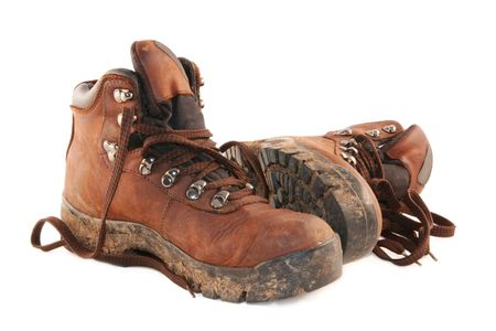dirty feet: A pair of muddy brown hiking boots, isolated on white.