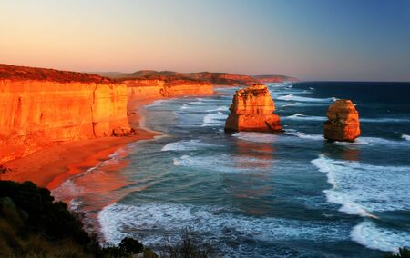 Two of the iconic Twelve Apostles glow red at sunset.  Victoria, Australia. Stock Photo