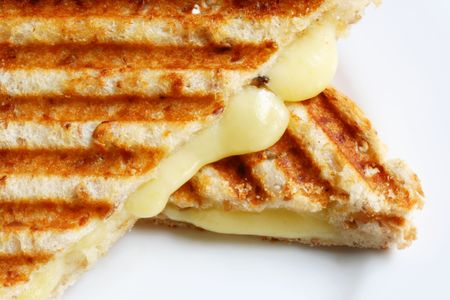 A grilled sandwich of melting cheese, on a white plate.  Wholewheat bread. Stock Photo
