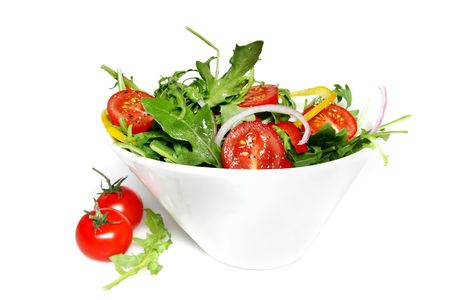 salad fork: A tossed green salad in a stylish white bowl, with cherry tomatoes. Stock Photo