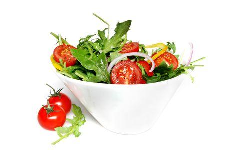 ensalada verde: Lanzaron una ensalada verde en un plato blanco con estilo, con tomates cherry.  Foto de archivo