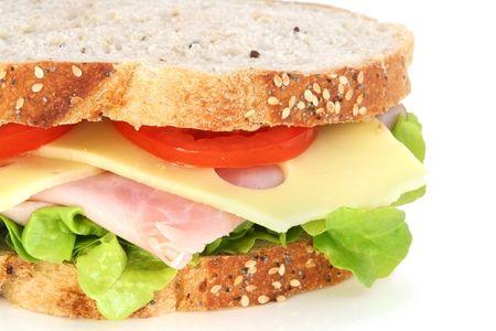 wholegrain mustard: Ham, cheese, lettuce and tomato sandwich on wholewheat sourdough bread. Stock Photo