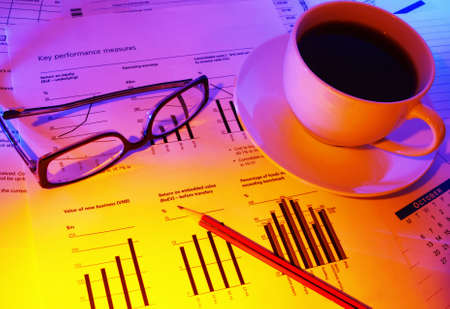 Late night checking financial performance.  Coffee for a caffeine boost, glasses and pencil on financial papers.  Warm tones. photo
