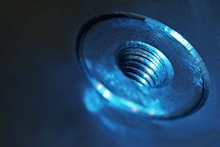 Metallic industrial background.  Threaded stainless steel in blue tone.  Detail of injection moulding tool.