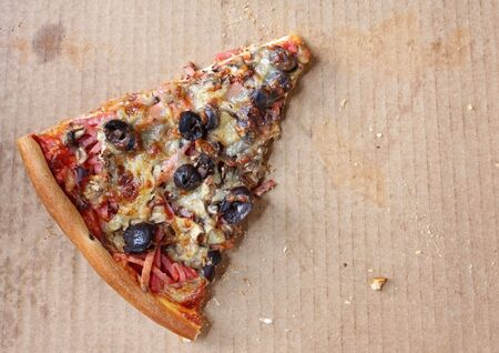 leftover: Last lonely slice of pizza, in pizza box.  Capricciosa, with black olives, ham, mushrooms,  and mozzarella.