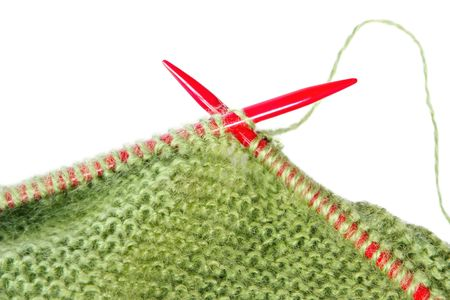 Knitting with green fluffy wool, on red knitting needles.  Close-up view, over white. Imagens