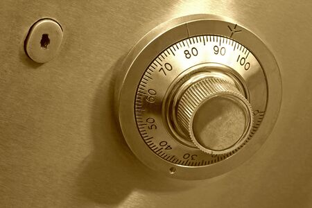 turn the dial: Combination safe lock, in golden duotone. Stock Photo