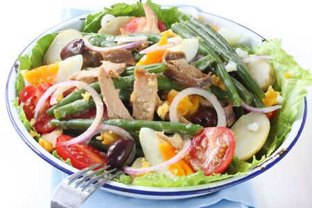 Salad nicoise.  Tuna, with green beans, grape tomatoes, eggs, chat potatoes, black olives, anchovies, and a vinaigrette mustard dressing. photo