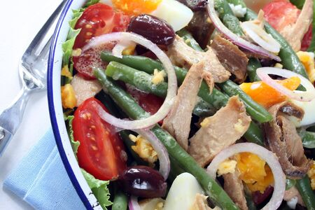 Salad Nicoise.  Tuna salad with green beans, eggs, chat potatoes, black olives, red onion, cherry tomatoes, anchovies, and a vinaigrette mustard dressing.  Delicious! photo