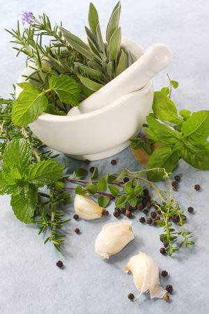 peppercorns: Mortar and pestle, with fresh herbs, garlic and peppercorns.