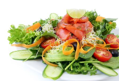 green's: Smoked salmon and avocado salad, isolated on white.  Mixed greens, tomatoes, carrots, black olives, cucumber and sprouts. Stock Photo