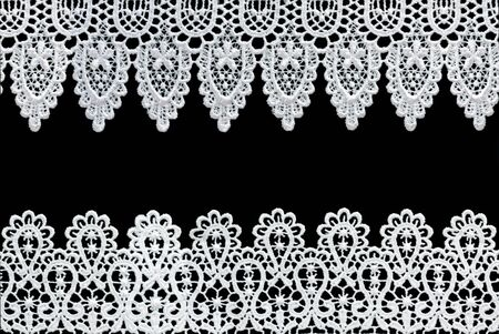 stitched: White lace forms a delicate border against black background.