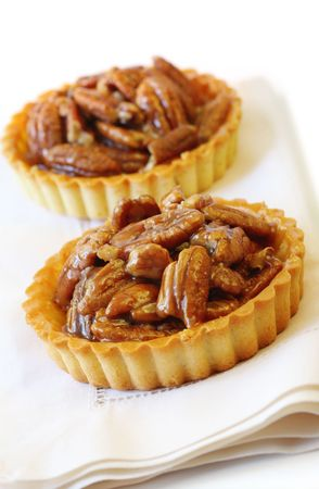 nutty: Little pecan tarts.  A luscious nutty dessert treat.  Shallow focus.