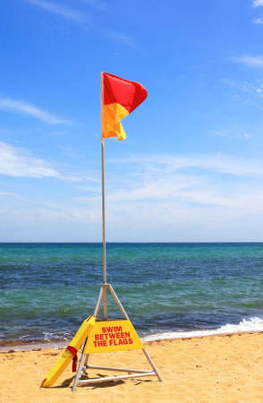 between: Australian beach safety flag - swim between the flags.