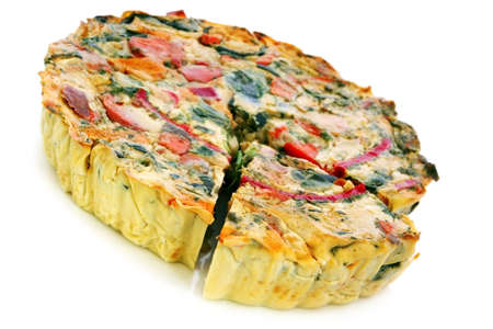 Roasted vegetable quiche, with a wedge cut out.  Delicious vegetarian food. photo