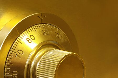 Golden toned combination safe lock, in close-up. photo