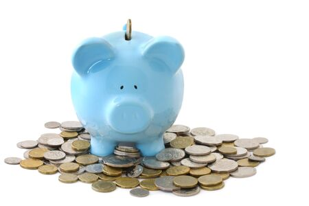 Overloaded blue piggy bank, surrounded by gold and silver coins. Stock Photo