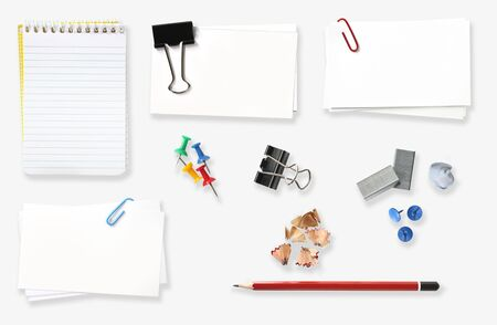tacky: Variety of office stationery, isolated on white.  Includes spiral notebook, blank labels, clip, push pins, staples, pencil and pencil shavings, paperclip, blue tacky gum.