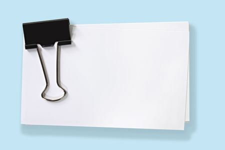 foldback: Stack of blank white cards fastened with black clip.