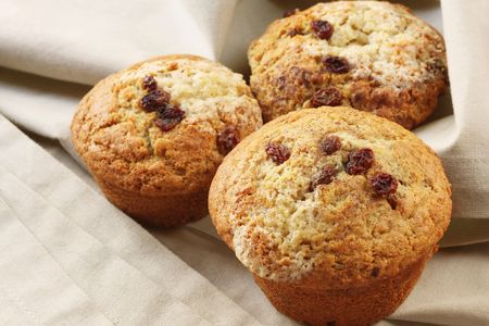 sultana: Home-baked cinnamon and sultana muffins, on beige linen.