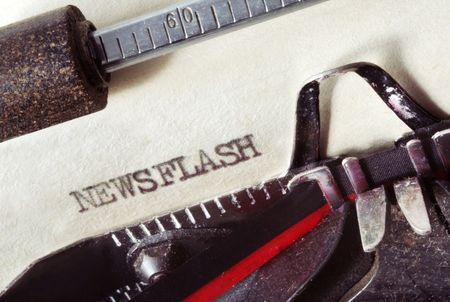 newsflash: Vintage typewriter with aged paper, showing the word Newsflash.  Close-up view, with lots of dust and great paper texture. Stock Photo
