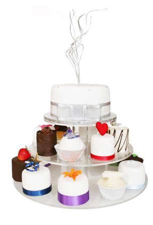 적합: Fancy little celebration cakes, on a tiered cake stand.  Isolated on white.  Suitable for wedding, birthday, or any other celebration.