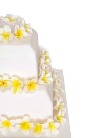 cake tier: Close-up of tiered wedding cake decorated with frangipani or plumeria flowers.